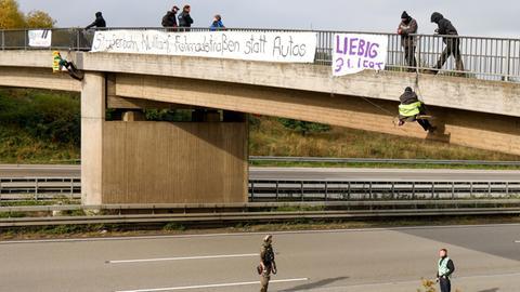 Umweltaktivisten hängen an einer Brücke über der Autobahn.
