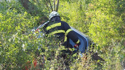 Ein Feuerwehrmann untersucht das Autowrack