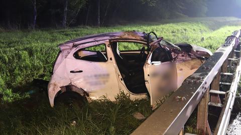 Das Wrack eines Autos liegt außerhalb der Leitplanke einer Autobahn.