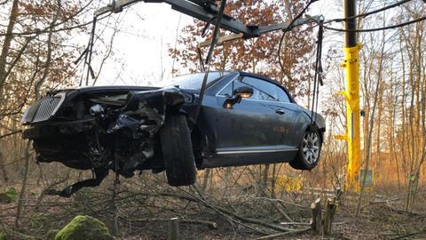 Ein Kran hebt das von der A5 abgekommene Luxusauto aus dem Waldstück bei Reiskirchen