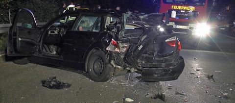 Beschädigtes Auto in der Nacht auf der Autobahn, im Hintergrund ein Feuerwehrwagen.