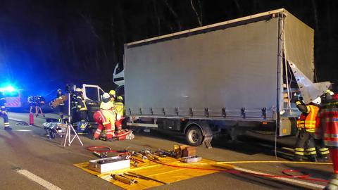 Feuerwehrleute arbeiten an einem Kleinlaster auf der Autobahn.
