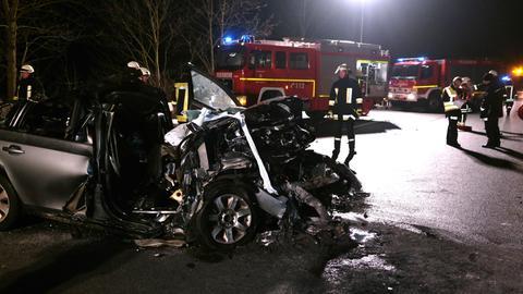 Demoliertes Auto, Feuerwehr im Hintergrund