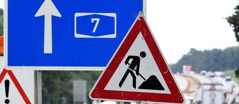 Baustellenschild vor einem A7-Autobahnschild.