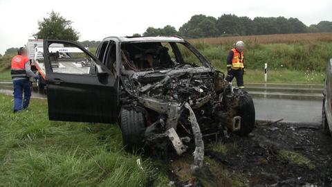 Helfer neben ausgebranntenm Auto auf Bundesstraße