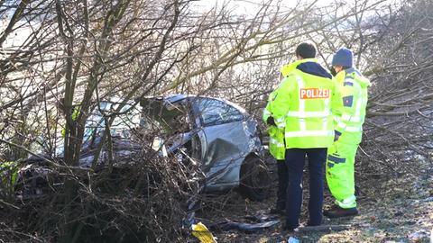 Polizisten sichern die Unfallstelle, das Auto steckt neben der Fahrbahn im Gestrüpp