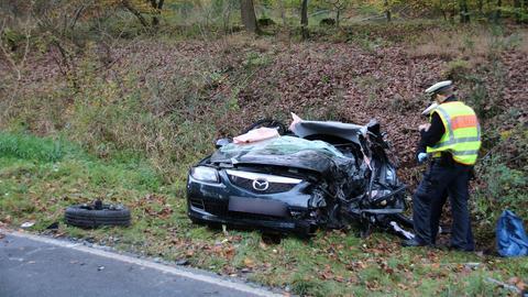 Autowrack im Graben und zwei Polizisten bei der Unfallaufnahme