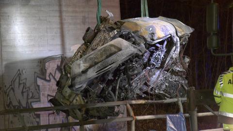 Ausgebranntes Autowrack wird von einem Abschleppdienst geborgen