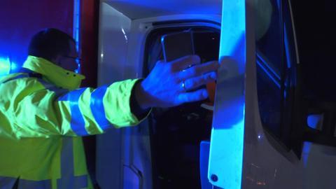 Ein Polizist nimmt einem Autofahrer das Handy ab.