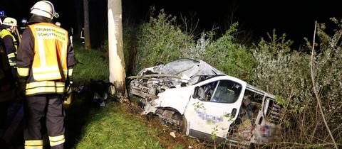 Einsatzkräfte am Unfallort - der Unfallwagen liegt mit starken Beschädigungen im Graben neben einem Baum.