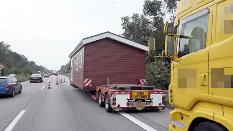 Ein braunes, einstöckiges Fertighaus - gepackt auf einem Schwertransportlaster - steht am rechten Fahrbahnrand der A67