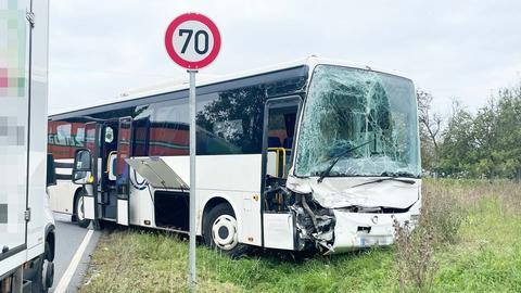 Ein beschädigter Bus und ein LKW nach einem Unfall am Straßenrand.