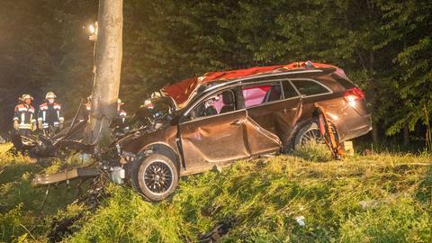 Unfallstelle auf Landstraße: Ein stark beschädigtes Auto, das offenbar gegen einen Baum gefahren ist. Dahinter stehen Einsatzkräfte