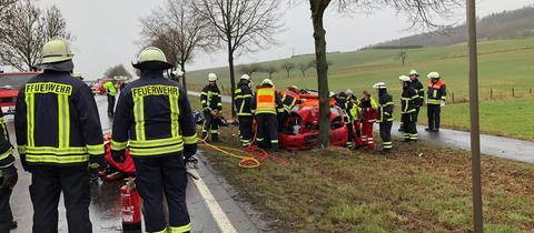 Einsatzkräfte an der Unfallstelle befreien den Beifahrer aus dem Fahrzeug, das frontal gegen einen Baum gefahren ist.