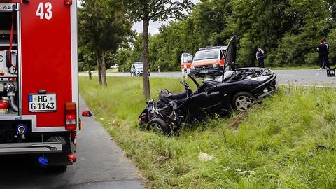 Die Unfallstelle in Grävenwiesbach mit dem zerstörten Wagen und Einsatzfahrzeugen von Feuerwehr und Rettungsdienst