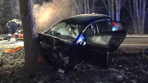 demoliertes Auto steht an einem Baum