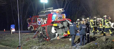 Feuerwehrleute stehen neben einem zerstörten, auf der Seite liegendem Wagen.