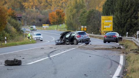 Auf einer Landstraße stehen zwei verunglückte Autos: Eine graue Mercedes A-Klasse, die an der linken Seite schwer getroffen wurde und ein schwarzer Audi in der Leitplanke.
