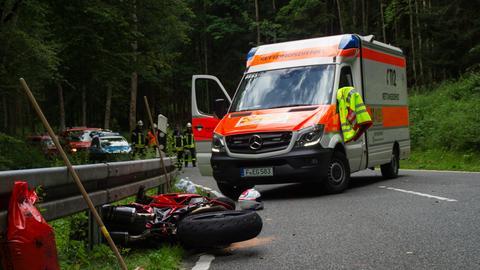 Ein Motorrad, dahinter ein Rettungswagen.
