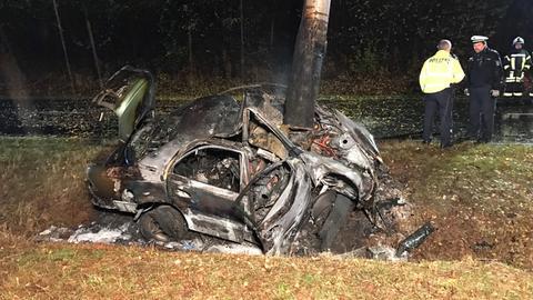 Der Rest eines verbrannten Autos, das gegen einen Baum gefahren ist.