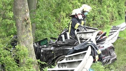 Zerstörtes Cabrio unter einer Leitplanke mit Feuerwehrmännern