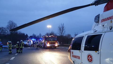Straße in der Dämmerung, mehrere Feuerwehreute stehen vor einem verunfallten Auto. Ein Rettungshubschrauber ist auf der Fahrbahn gelandet.