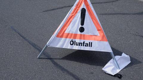 Ein aufgestelltes Schild warnt vor einem unfall durch eine Ölspur