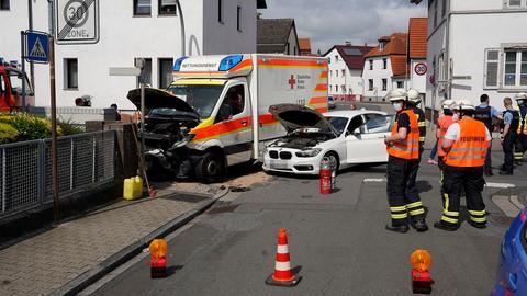 Der Rettungswagen und das zweite Unfallauto stehen auf einer Straße, davor Feuerwehrleute und Polizisten.