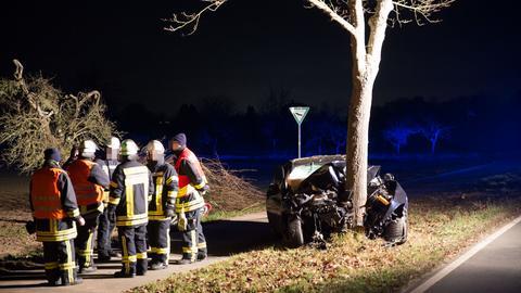 Zerstörtes Auto am Baum, Feuerwehrmänner