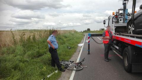 Unfallstelle mit kaputten Rad und Abschleppwagen