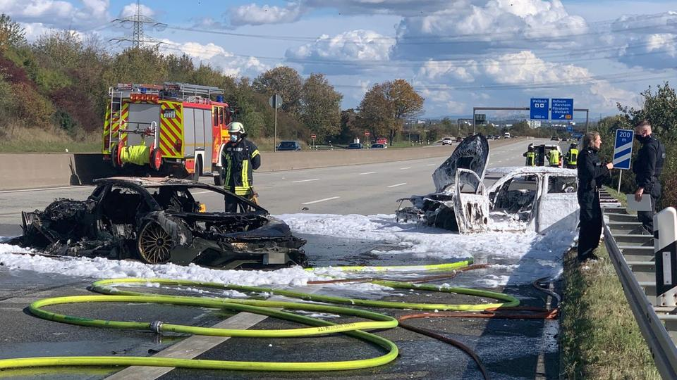 Zwei völlig ausgebrannte Autos liegen auf der Fahrbahn. Sie sind von Löschschaum bedeckt. Feuerwehrleute stehen daneben.