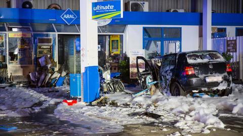 Ein ausgebranntes Autowrack auf einer Tankstelle mit Löschschaum