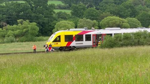 Einsatzkräfte stehen neben der Regionalbahn, die gerade eine Frau überfahren hat.