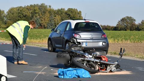 Unfallstelle mit Motorradwrack und beschädigtem Pkw
