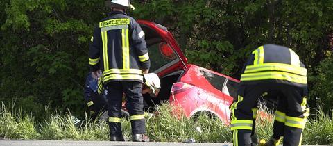 Feuerwehrleute bergen einen tödlich verunglückten Autofahrer aus seinem Wagen in Trebur (Groß-Gerau)