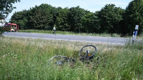 Ein kaputtes Fahrrad liegt neben der Straße im Gras, im Hintergrund steht ein Einsatzwagen, ein Helfer läuft die Straße entlang