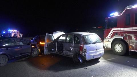 Eines der Unfallfahrzeuge hat eine demolierte Motorhaube. Daneben steht ein Feuerwehrauto.