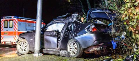 Ein demoliertes Auto steht neben einer Straßenlaterne, dahinter parkt ein Rettungswagen.