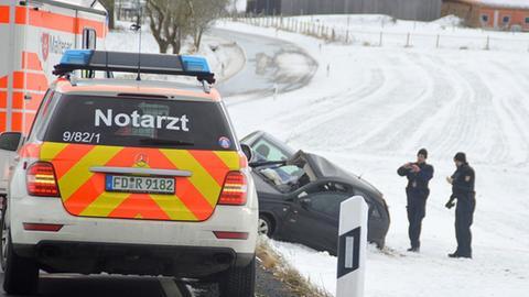 Ein Notarztwagen am Straßenrand, im Hintergrund zwei Autos auf verschneitem Feld.