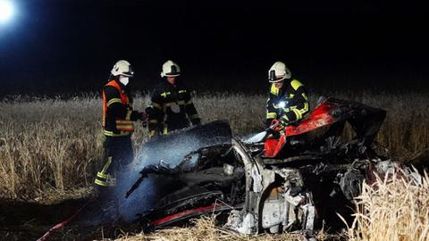 Das Autowrack liegt auf einem Feld, Feuerwehrleute stehen drum herum.