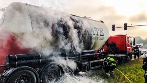 Feuerwehrmänner löschen den brennenden Lkw.