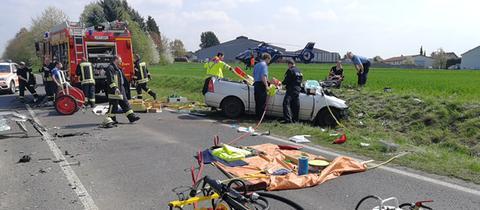 Autowrack im Graben, Einsatzkräfte , Rettungshubschrauber im Hintergrund