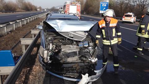 Ein Feuerwehrmann steht neben einem vollständig demolierten Auto.
