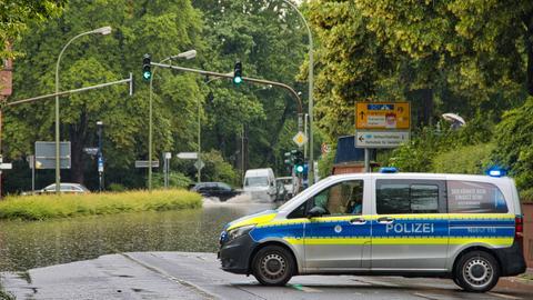 Die Polizei sichert eine überflutete Straße in Offenbach ab.