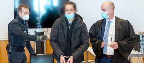 Der Angeklagte steht in der Mitte zwischen seinem Anwalt und einem Polizeibeamten. Er trägt Handschellen. Sein Gesicht ist unkenntlich gemacht.