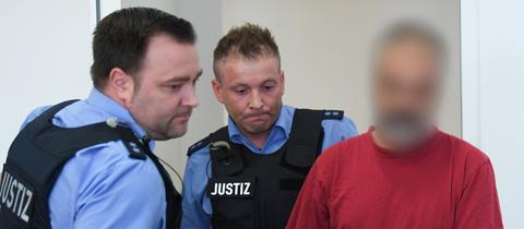 Der Angeklagte mit zwei Justizbeamten im Hanauer Mordprozess