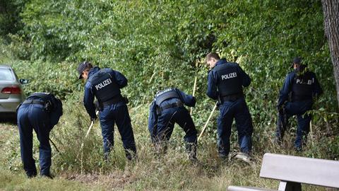 Polizisten suchen am Fundort der Tasche mit den Knochen nach weiteren Spuren.