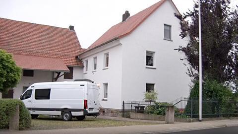 Ein weißer Transporter steht im Hof eines Gutes neben dem Wohnhaus.