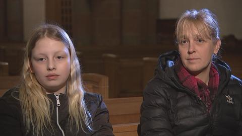 Tochter und Mutter sitzen auf Kirchenbank
