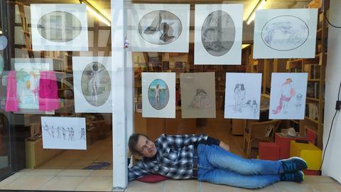 """Künstler Achim Gogler liegt im Schaufenster der Wächtersbacher Buchhandlung """"Dichtung & Wahrheit"""", die mit Goglers Aktgemälden zur Verkehrsberuhigung beiträgt."""